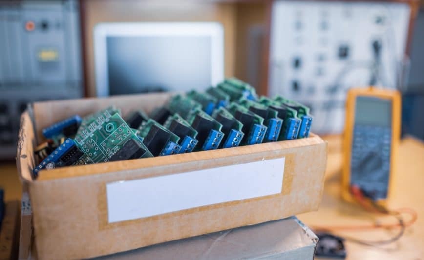 Des microcircuits intégrés verts en gros plan sont empilés dans une boîte pour se préparer à la suite en usine pour la production d'équipements
