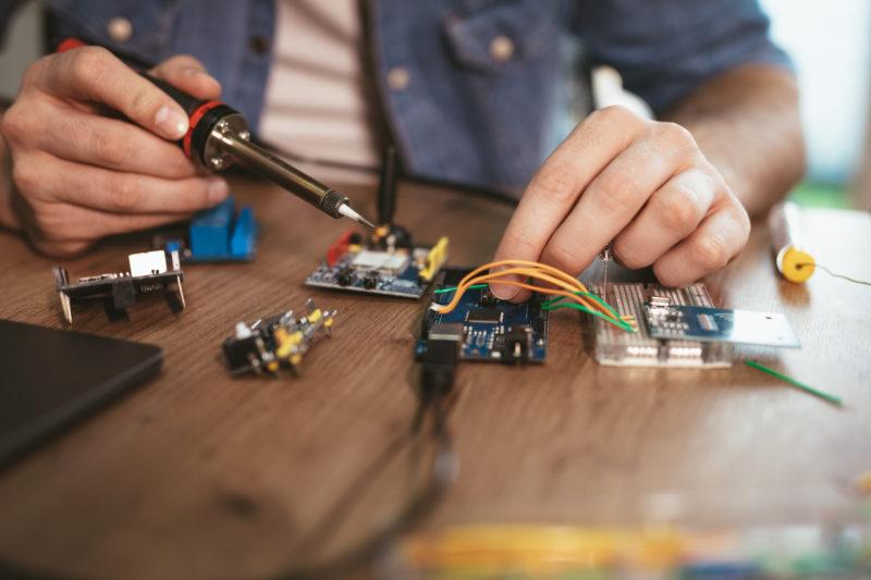 Un technicien soldat une carte électronique